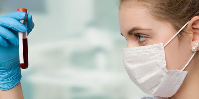 Bluttest zur Diagnose von Allergien des Soforttyps Typ 1. Bild: Frau mit Bundschutz und Gummihandschuhen hält Blutprobe in Reagenzglas in der Hand und betrachtet es.