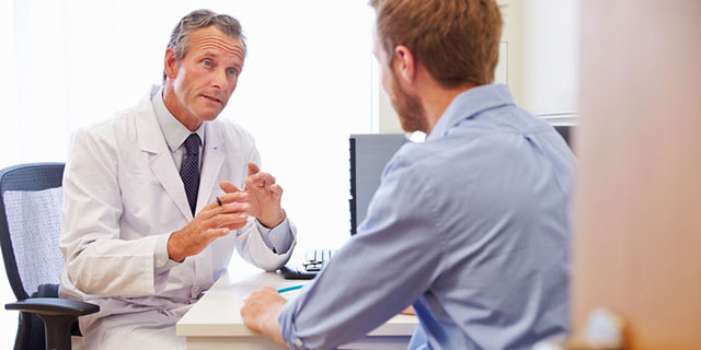 Arztgespräch (Anamnese) zur Allergie-Diagnose. Bild: Arzt spricht am Schreibtisch mit einem Patienten.