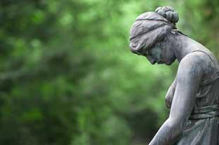 Psychische Risikofaktoren bei der Entstehung von Allergien Bild: Steinstatue einer Frau die den Kopf stark nach unten neigt.