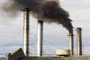 Rauchende Schornsteine einer Fabrik, schwarzer Rauch.