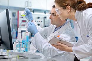 Ein Wissenschaftler und eine Wissenschaftlerin in weißen Kitteln arbeiten im Labor. Er hält einen mit gelber Flüssigkeit gefärbten Glaskolben, sie hält einen Schreibblock. - © Alexander Raths/fotolia