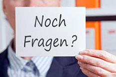 """Frau Hält Zettel mit dem Satz """"Noch Fragen?"""" in die Höhe."""