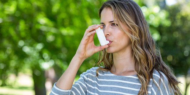 Junge Frau benutzt ein Asthmaspray im Freien