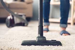 Großaufnahme eines Staubsaugers, mit dem eine Person einen hellen Teppich absaugt.