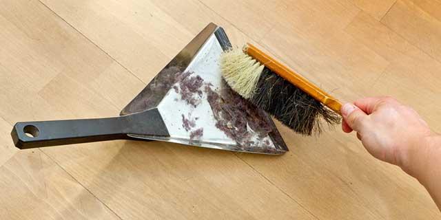 Ein Kehrblech liegt auf einem Holzfußboden. Die Hand eines Mannes kehrt mit einem Handbesen Staub darauf.