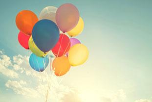 Ein Bündel verschiedenfarbiger Luftballons fliegt in den Himmel