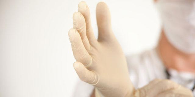 Großaufnahme einer Hand, die in einen Latexhandschuh schlüpft