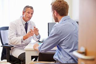Ein junger Mann im Gespräch mit einem Arzt. Der Patient ist von hinten zu sehen, der Arzt von vorne