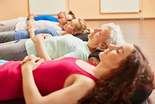 Vier Personen unterschiedlichen Alters in Sportkleidung liegen mit geschlossenen Augen auf dem Rücken in einer Sporthalle und entspannen sich