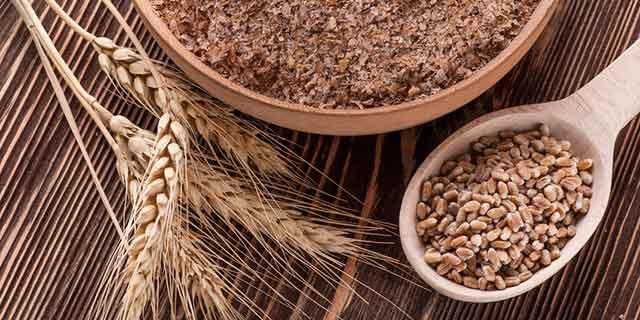 Weizenkörner auf einem Holzlöffel und in einer Holzschale, daneben Weizenähren