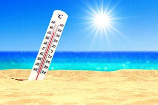 Foto zeigt Thermometer, das 35 Grad Celsius anzeigt und im Sand eines Strands steckt. Im Hintergrund ist das Meer mit blauem Himmel und der Sonne.