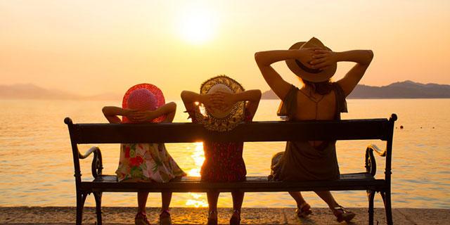 Mutter und zwei Töchter genießen den Sonnenuntergang auf einer Bank am Meer - vermutlich ohne Angst vor Sonnenallergie
