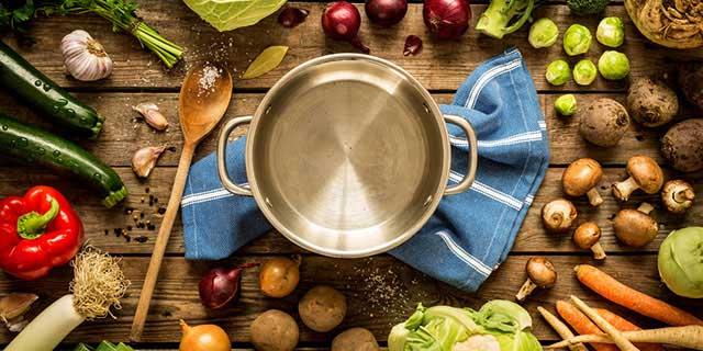 In der Mitte steht ein Kochtopf auf einem blauen Küchenhandtuch, daneben ein Kochlöffel aus Holz. Darum herum sind verschiedene Gemüsesorten wie Lauch, Karotten, Rosenkohl, Zucchini, Champignons und Blumenkohl platziert