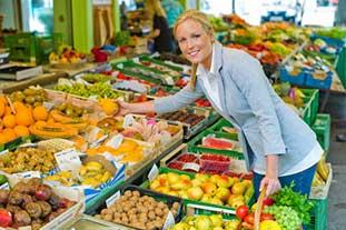 Eine Frau beugt sich über eine Obstauslage. In der linken Hand hält sie einen Korb mit Gemüse, in der rechten Hand eine Orange