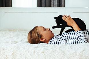 Mädchen liegt auf einer Decke und spielt mit einer schwarzen Katze, die auf ihrem Bauch liegt. Für Kinder mit Katzenllergie ist das ein Problem.