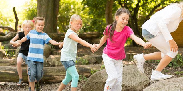 Das Foto zeigt vier Kinder, die Hand in Hand im Freien spielen und über umgefallene Baumstämme und große Steine klettern.