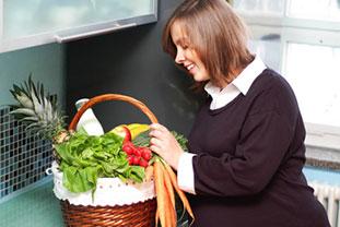 Eine schwangere Frau steht in der Küche vor einem Einkaufskorb, der voll mit gesunden Lebensmittel, wie Salat, Radieschen, Ananas und Milch ist.