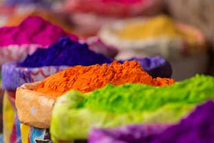 Foto zeigt die Farbstoffe lila, grün, orange, blau, pink und gelb in Pulverform. Sie befinden sich in Gefäßen, die dicht hintereinander stehen.