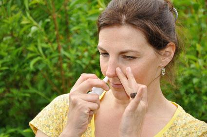 Frau, die gegen die Symptome ihres allergischen Schnupfens ein Nasenspray einnimmt