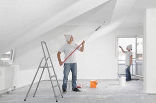 Zeigt zwei Maler, die einen Raum unter dem Dach streichen. Der Raum hat eine Dachschräge und eine Gaube. Der Boden ist mit Folie abgeklebt, in der Mitte steht eine Leiter und zwei Farbeimer.