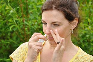 Junge Frau im Freien sprüht Nasenspray in ihr rechtes Nasenloch und verschließt das linke Nasenloch mit der anderen Hand