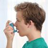 Junge wendet ein Asthmaspray an