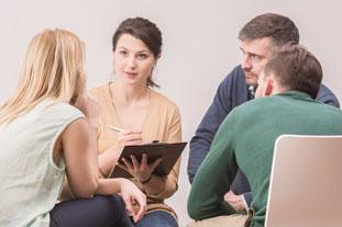 Eine Gruppe mit vier jungen Menschen sitzt in einem Gesprächskreis und unterhält sich