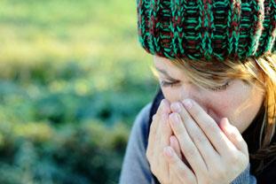 Frau mit Heuschnupfen-Symptomen putzt sich im Freien die Nase