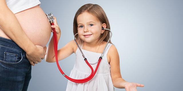 Ein kleines Mädchen hört mit einem Stethoskop den Bauch einer schwangeren Frau ab