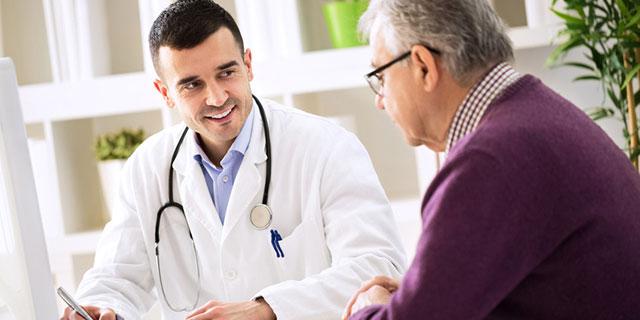 Grauhaariger Mann im Gespräch mit einem Arzt