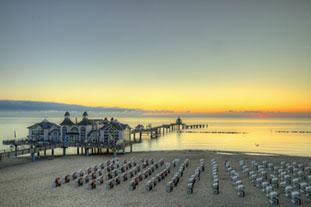 Blick aufs Meer mit einem Steg der aufs Meer hinauf geht. Im Vordergrund Strandkörbe am Strand.