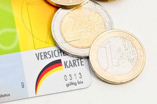 Eine Krankenversicherungskarte mit einigen Euromünzen.