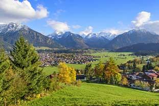 Blick ins Oberallgäu. Wiesen, Bäume, Häuser. Im Hintergund die Berge und blauer Himmel.