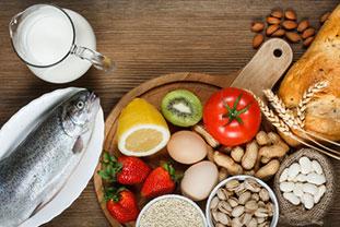 Verschiedene Lebensmittel auf einem Tisch, darunter Fisch Milch, Eier, Nüsse, Obst und Gemüse