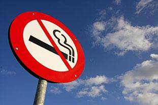 Verkehsschild vor blauem Himmel. Das Schild zeigt eine durchgestrichene Zigarette.