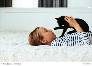 Kind liegt auf weicher Flauschdecke und hält eine junge schwarze Katze vor der Brust