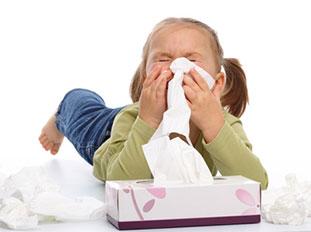 Kleines Mädchen mit einer Taschentücherbox putzt sich die Nase, drum herum liegen bereits benutzte, zusammengeknüllte Taschentücher