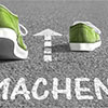 grüne Laufschuhe auf der Tartanbahn, darunter das Wort Machen!