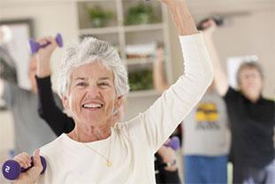 Weißhaarige Seniorin in der Gymnastik-Gruppe