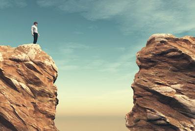 Junger Mann steht auf einem Felsen am Rande einer engen Schlucht und blickt zur anderen Seite der Schlucht