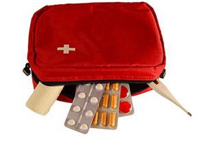Zeigt eine Reiseapotheke, in Form einer kleinen roten Tasche mit einem weißen Kreuz darauf und einem geöffneten schwarzen Reißverschluss. Aus der Tasche schauen drei Medikamentenblister mit unterschiedlichen Pillen sowie ein Fieberthermometer und ein Pflaster heraus.