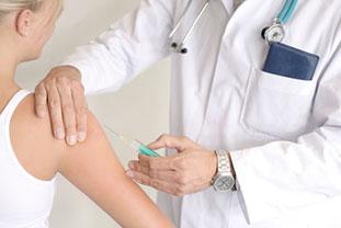 Spezifische Immuntherapie mit Spritze Bild: Arzt verabreicht einer Patientin eine Spritze in den Oberarm.