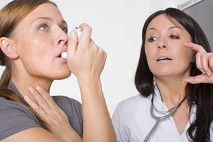 Cortison in der Allergie-Therapie. Bild: Ärztin erklärt einer Patientin gestenreich wie man einen Inhalator benutzt.