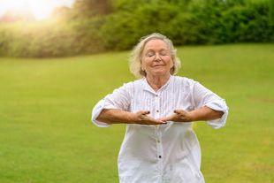 Seniorin im Freien bei Atemübungen bei Asthma bronchiale