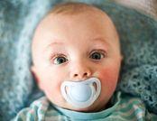 Großaufnahme des Kopfes eines Babys mit hellblauem Schnuller, die Wangen sind, wie für Neurodermitis bei Säuglingen typisch, gerötet
