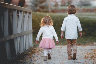 Kleines Mädchen und etwas größerer Junge von hinten aufgenommen beim Spaziergang - © Kevin Gent/unsplash.com