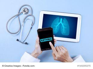 Hände eines Arztes halten ein Smartphone auf dem Asthma steht, ein Tablet mit einer Grafik, die eine Lunge zeigt und ein Stetoskop