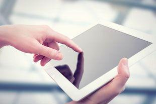 Großaufnahme eines weißen Tablets, das mit der rechten Hand gehalten und mit dem linken Zeigefinger bedient wird