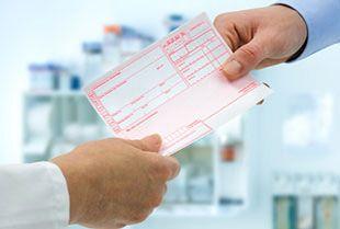Ein Arzt überreicht einem Patienten ein Rezept