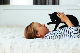 Mädchen spielt mit Katze